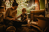 little boy with his mother looking at book in front of the Christmas tree, Christmas, family