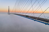France, between Calvados and Seine Maritime, the Pont de Normandie (Normandy Bridge) emerges from the morning mist of autumn and spans the Seine to connect the towns of Honfleur and Le Havre