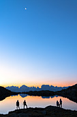 Hikers admiring Brenta Group Dolomites reflected in Lago Nero di Cornisello at dawn, Trento,Trentino-Alto Adige, Italy, Europe