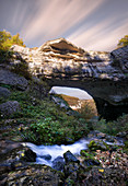 Waterfall flowing below Veja bridge, a huge natural arch in Lessinia, Veneto, Italy, Europe