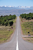 Long tarred road with the snowy Atlas Mountains in the background, Morocco, North Africa, Africa