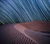 Equatorial star trail above sand dunes in the Rub al Khali desert, Oman, Middle East