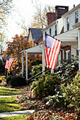 American flags hanging in front of Suburban Houses