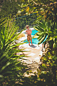 Rear View of Young Shirtless Boy standing near Swimming Pool