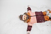 Canada, Ontario, Girl (2-3) doing snow angels