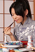 Young woman in kimono eating traditional Japanese meal with chopsticks