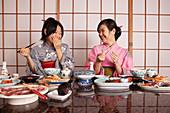 Happy young women in kimonos eating dinner in restaurant