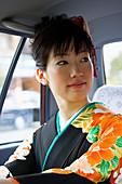 Beautiful Japanese woman in kimono in back seat of taxi