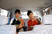 Portrait Japanese women in kimonos riding in back seat of car