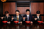 Japanese business people in suits eating ramen with chopsticks in restaurant
