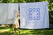 Girl (6-7) with laundry in backyard