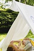 Girl (6-7) and boy (4-5) relaxing in homemade tent in backyard