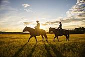 USA,Utah,Salem,Father and daughter (14-15) riding horses at sunset