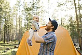 Father lifting baby boy(6-11 months) by tent in Uinta-Wasatch-Cache National Forest