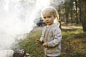 Portrait of girl (2-3) roasting marshmallow over campfire,Wasatch Cache National Forest