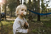 Portrait of girl (2-3) eating marshmallow in forest,Wasatch Cache National Forest
