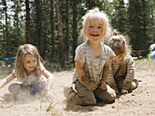 Three smiling girls (2-3,4-5) playing in sand on camping,Wasatch-Cache National Forest