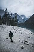 Italy,Pragser Wildsee,Dolomites,South Tyrol,Man at lake shore among stone stacks