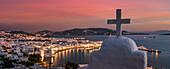 Greece,Cyclades Islands,Mykonos,Chora,Cross on church with coastal village in background