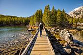 USA,Wyoming,Jackson,Grand Teton National Park,Senior woman walking on wooden path over Taggart Lake in Grand Teton National Park