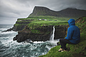 Denmark,Faroe Islands,Gasadalur Village,M?Lafossur Waterfall,Man sitting on edge of cliff and looking at Mulafossur Waterfall