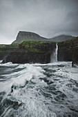 Denmark,Faroe Islands,Gasadalur Village,M?Lafossur Waterfall,Coastline with Mulafossur Waterfall falling into Atlantic Ocean in stormy day