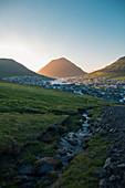 Denmark,Faroe Islands,Klaksvik,Landscape with mountains and village by sea at dawn