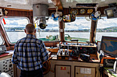 Captain on boat, crossing to the fortress island Munkholmen, Trondheim, Norway
