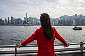 Woman in red blazer admires the view from the Tsim Sha Tsui side of Victoria Harbor with the Hong Kong skyline in the distance, Hong Kong, Hong Kong, China, Asia
