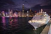 Cruise ship Silver Shadow at the Hong Kong Cruise Terminal with city skyline at dusk, Hong Kong, Hong Kong, China, Asia