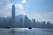 Silhouette of the Kowloon Ferry in Victoria Harbor with the Hong Kong skyline behind it, Hong Kong, Hong Kong, China, Asia