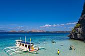 Luftaufnahme von traditionellem philippinisches Banca Auslegerkanu und Gäste, die Wasseraktivitäten am Strand 91 auf der Insel Coron genießen, Banuang Daan, Coron, Palawan, Philippinen, Asien