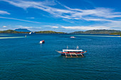 Aerial view of a traditional Filipino Banca outrigger canoe tour boat, a tender boat and the cruise ship Silver Shadow at anchor in the distance, Barangay I, Romblon, Romblon, Philippines, Asia