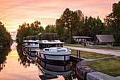 Three Le Boat Horizon houseboats docked at Beveridge Locks on the Tay River with Parks Canada campsite at sunset, near Lower Rideau Lake, Ontario, North Canada, North America