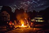 Menschen entspannen sich am Lagerfeuer bei Vollmond auf dem Parks Canada Campingplatz an den Schleusen Beveridge Locks am Fluss Tay River mit einem angedockten Le Boat Horizon Hausboot bei Nacht, nahe Lower Rideau Lake, Ontario, Kanada, Nordamerika