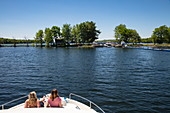 Two young women relax on the bow of a Le Boat Horizon houseboat as it approaches the lock at Narrows Lockstation, Lower Rideau Lake, Ontario, Canada, North America