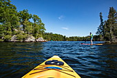 Tip of a yellow kayak and man on SUP stand-up paddleboard on Indian Lake, near Chaffey's Lock, Ontario, Canada, North America