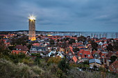 Terschelling lighthouse and town with marina at dusk seen from the hill, West Terschelling, Terschelling, West Frisian Islands, Friesland, Netherlands, Europe