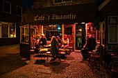People sit in front of Café 't Zwaantje and enjoy beer at night, West Terschelling, Terschelling, West Frisian Islands, Friesland, Netherlands, Europe