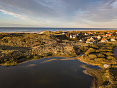 Aerial view of holiday homes by a lake and in the midst of dunes along the North Sea coast at sunset, Midsland aan Zee, Terschelling, West Frisian Islands, Friesland, Netherlands, Europe