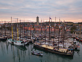 Aerial view of historic flat bottom sailing boats in the harbor of West Terschelling with town and Brandaris lighthouse at sunset, West Terschelling, Terschelling, West Frisian Islands, Friesland, Netherlands, Europe