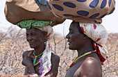 Angola; western part of the province of Cunene; two women by the roadside; carrying her luggage on her head