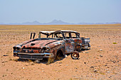 Angola; in the southern part of Namibe Province; Desert in Iona National Park; End of dry season; Gravel plain and extensive grassy areas; Wreck of a vintage car; Spare parts were cannibalized
