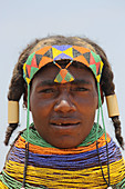 Angola; Huila Province; small village near Chibia; Muhila woman with typical neck and headdress; massive choker made of pearl necklaces and earth