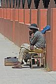Angola; Provinz Huila; Provinzhauptstadt Lubango; Schuhputzer im Stadtzentrum wartet auf Kundschaft