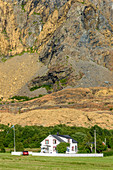 House in front of cliff with serpentinite and olivine stone, Leka island, Norway