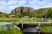 Cyclists on small bridge with red houses in front of Torghattan, Bronnoysund, Norway