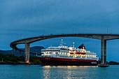 Hurtigruten ship under bridge over the sound, Bronnoysund, Norway