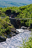 Suspension bridge with people, mountain panoramas and gorges along the Silvervägen (R 77) to Junkerdal, Norway