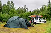Family camping in the wild by the Vefsna river, Norway